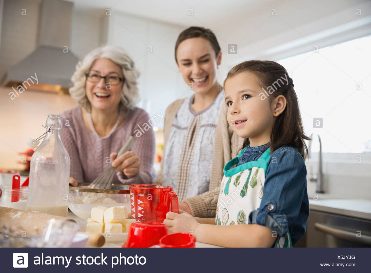 Three generation family baking together in kitchen - Stock Image