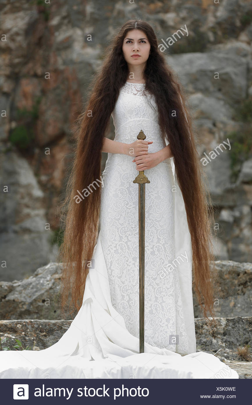 Reminiscence to Joan of Arc, Jeanne d'Arc, young woman in a white dress with a sword - Stock Image