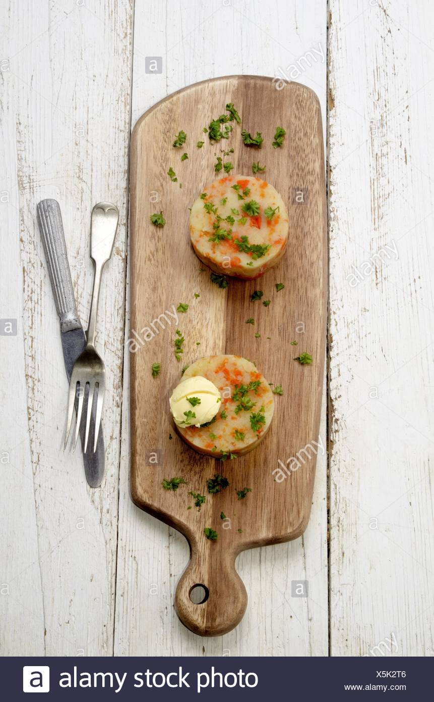 mashed potatoes with carrots, butter and parsley on a wooden board. - Stock Image