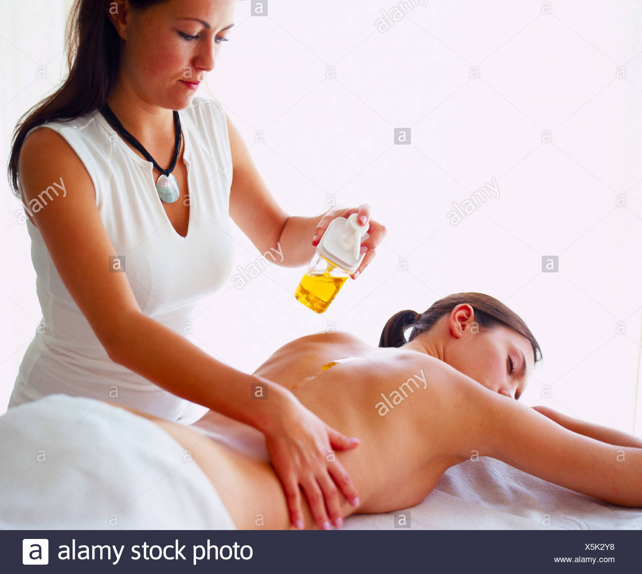 Rear view of young woman getting back massage from massage therapist - Stock Image