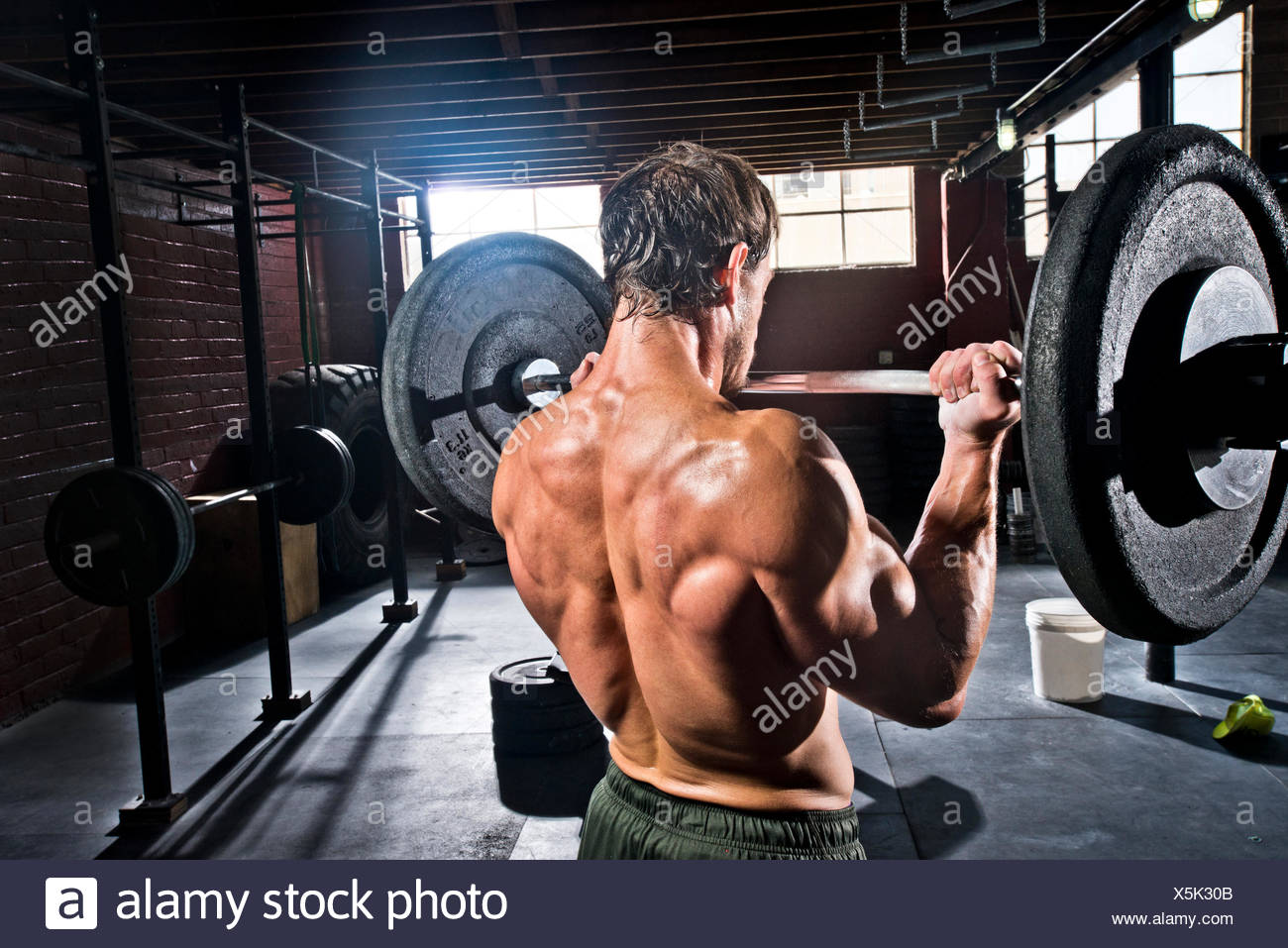 A crossfit athlete performs bicep curls. - Stock Image