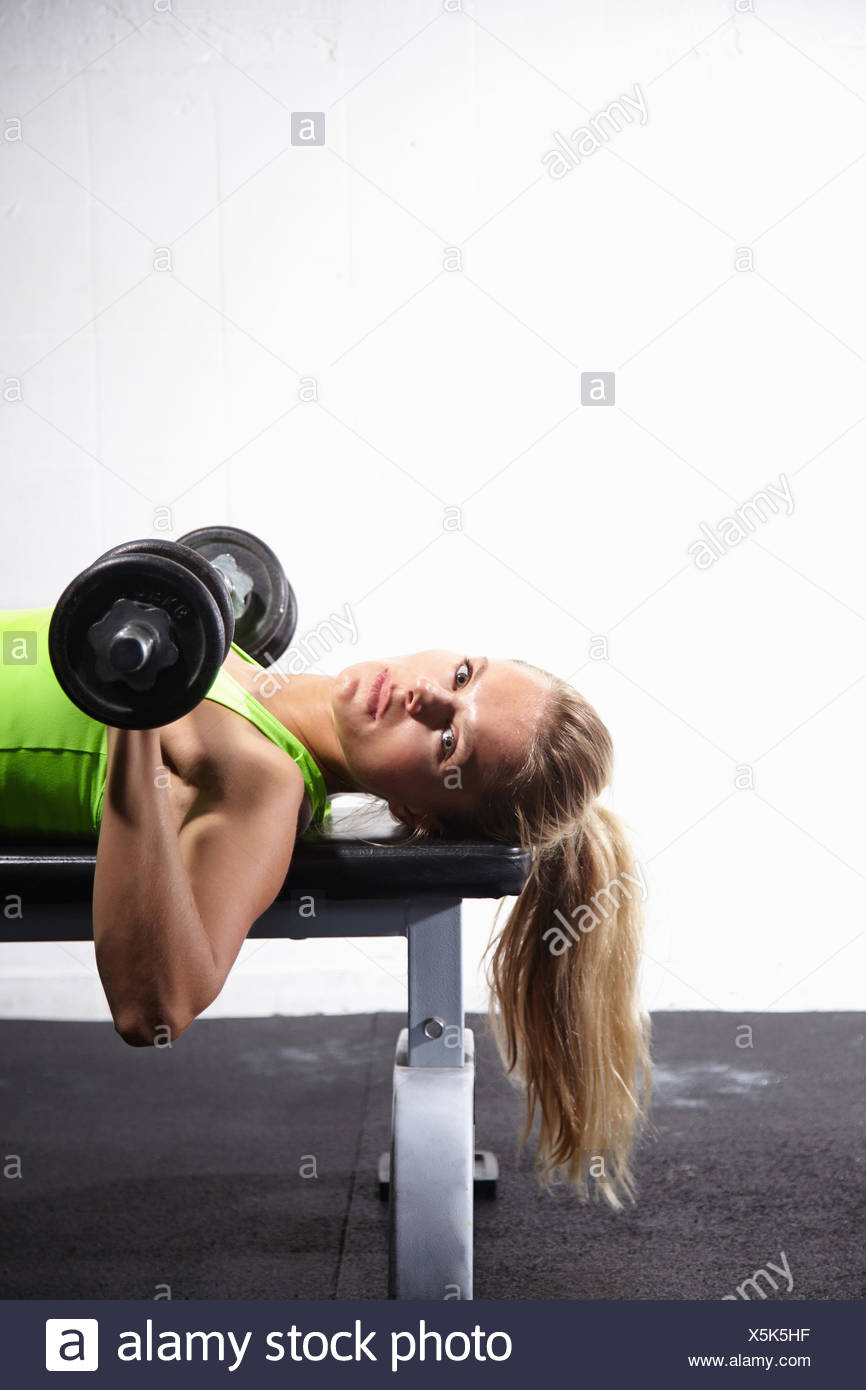 Young woman lying on bench training with bar bell in gym - Stock Image