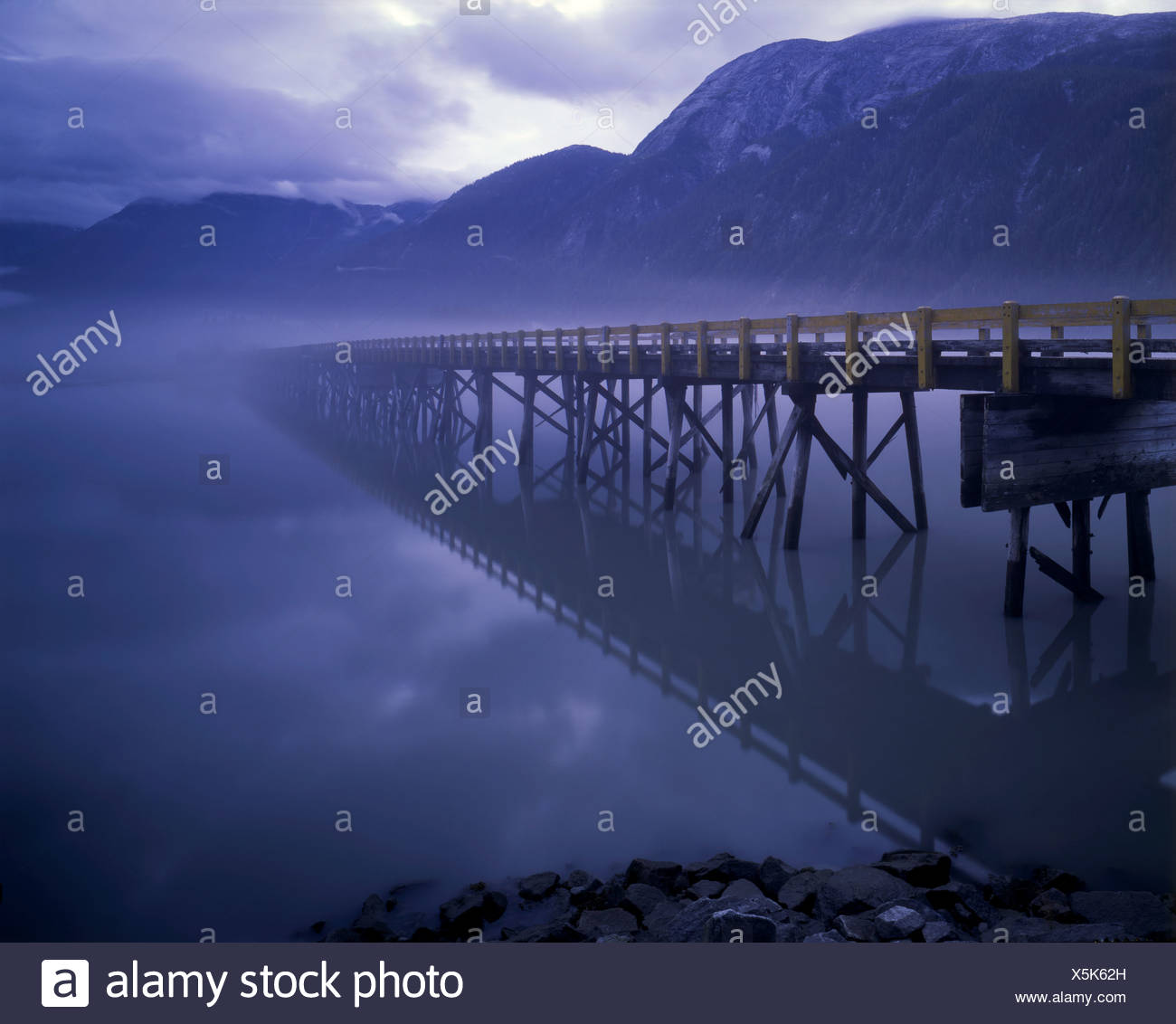 Alaska. Hyder. Bridge to Nowhere. Bridge dissolving into a rainforest mist in Alaska's Southeast region. - Stock Image