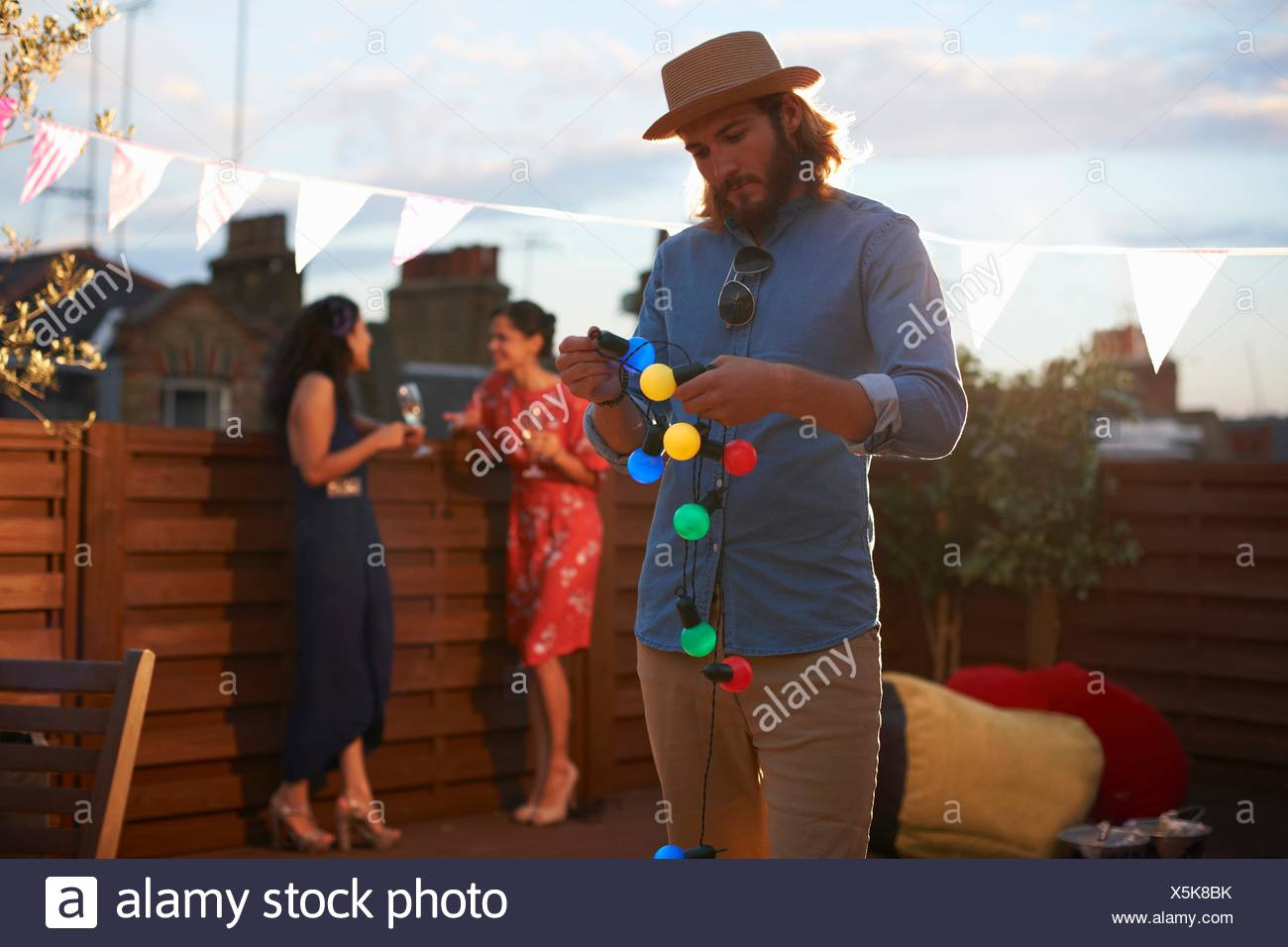 Man hanging garden lights for early evening party - Stock Image