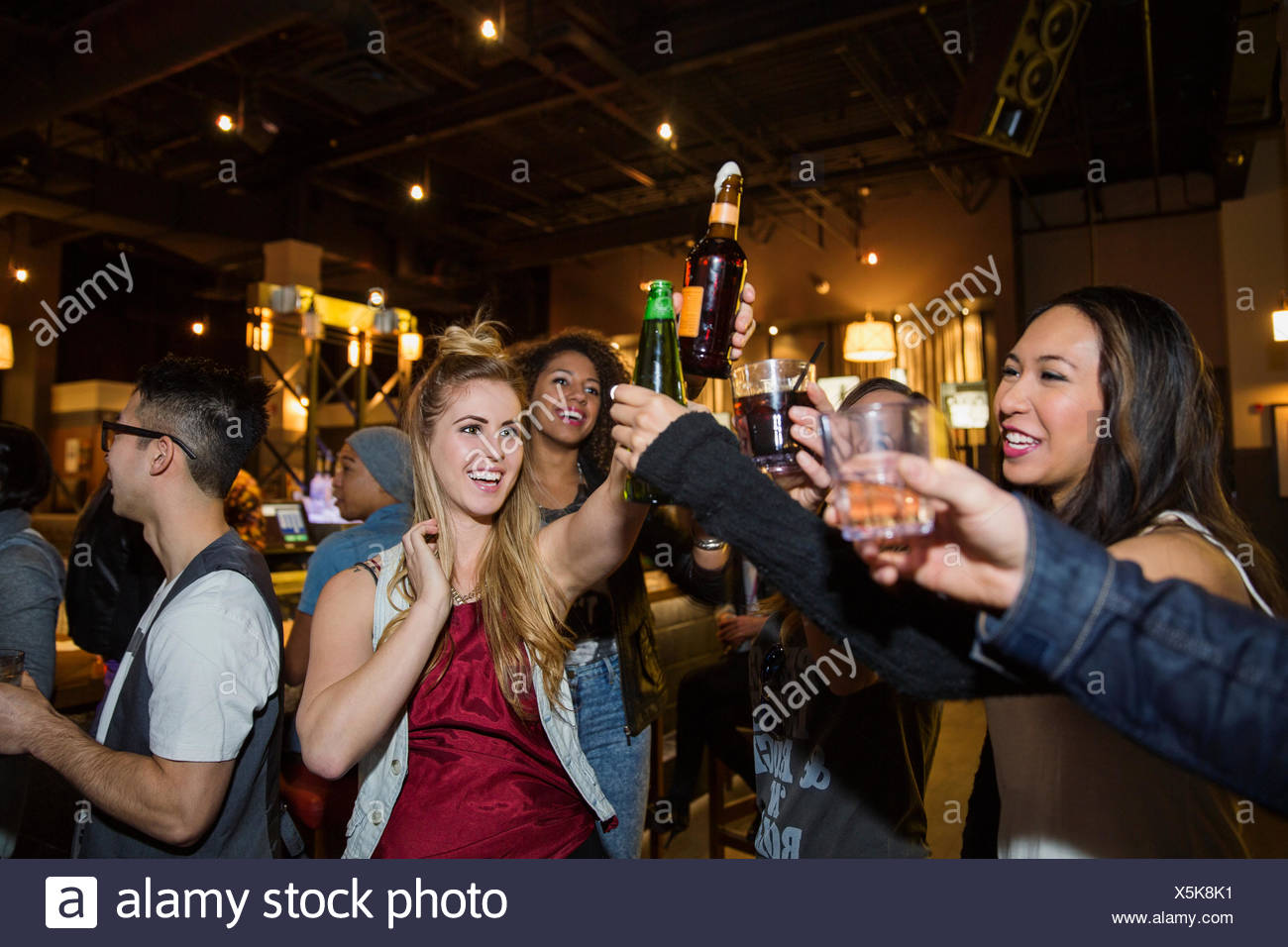 Friends toasting cocktails at bar - Stock Image