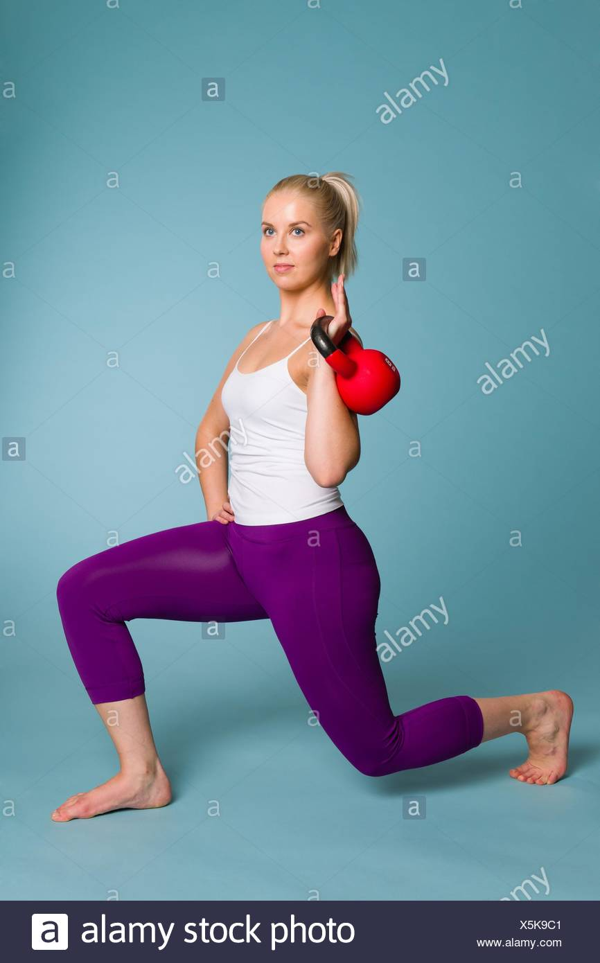 Fitness Girl On Squat Position With A Kettlebell