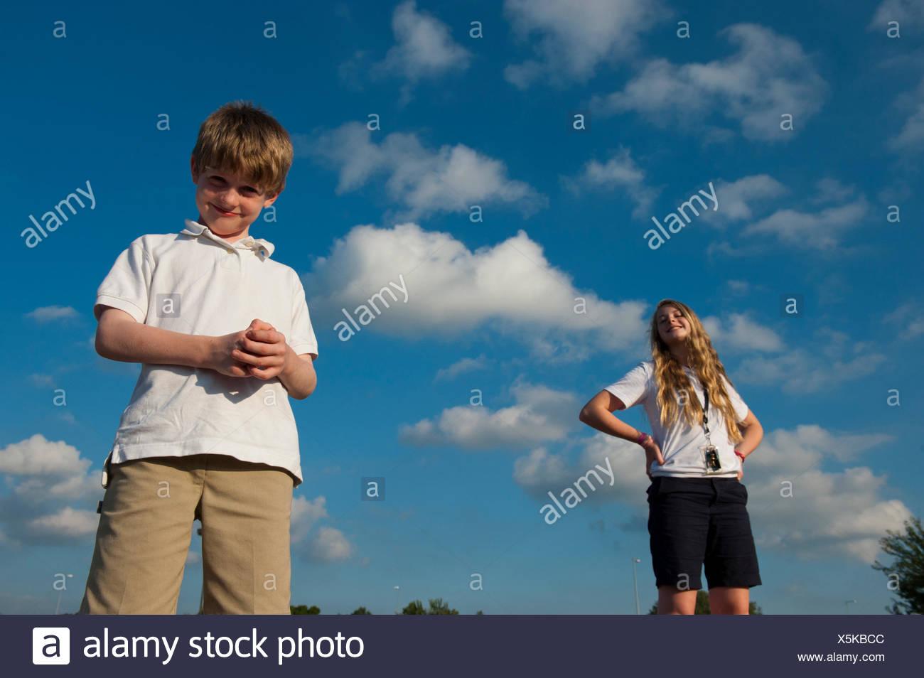 Siblings pose in their school uniforms. - Stock Image