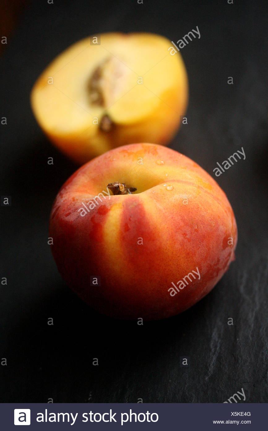 Fresh peach and halved peach - Stock Image