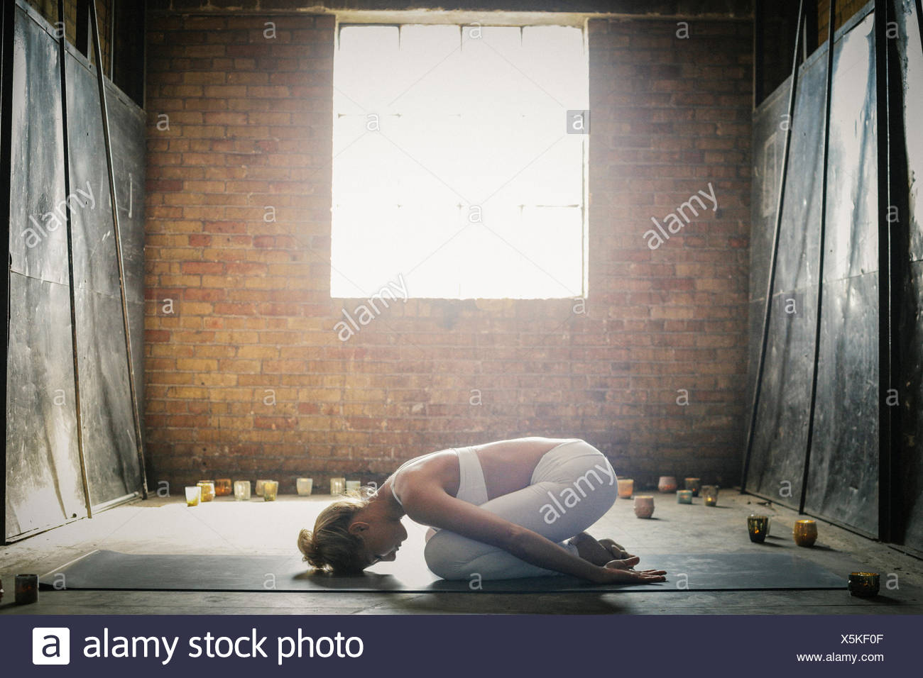A blonde woman in a white crop top and leggings,kneeling on a mat on the floor surrounded by candles. - Stock Image