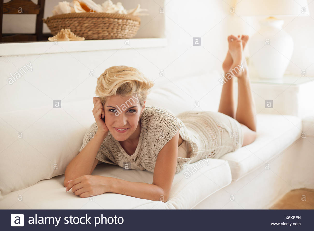Smiling woman relaxing on sofa - Stock Image