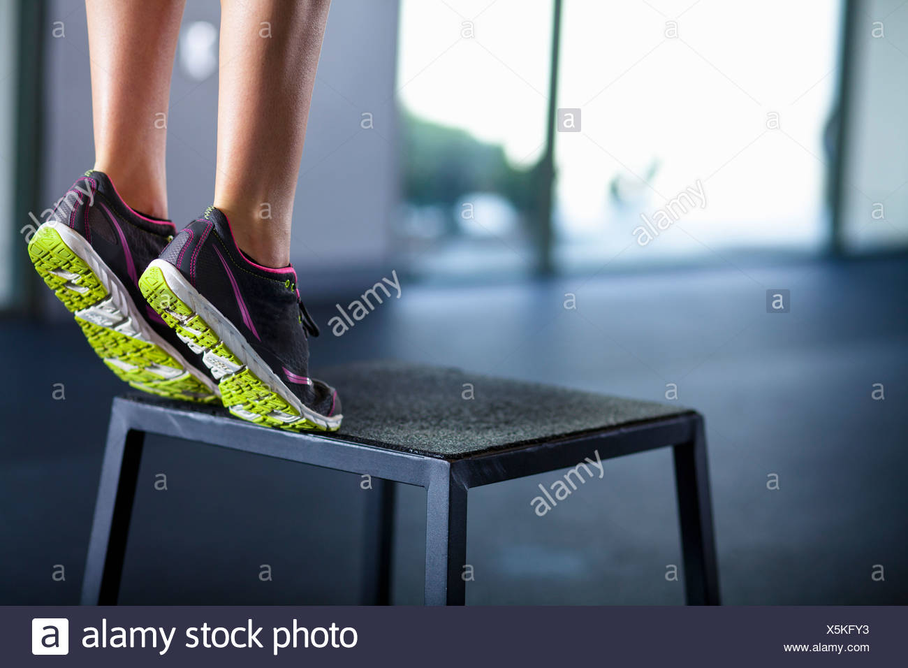 Young woman tiptoeing on edge of stool - Stock Image