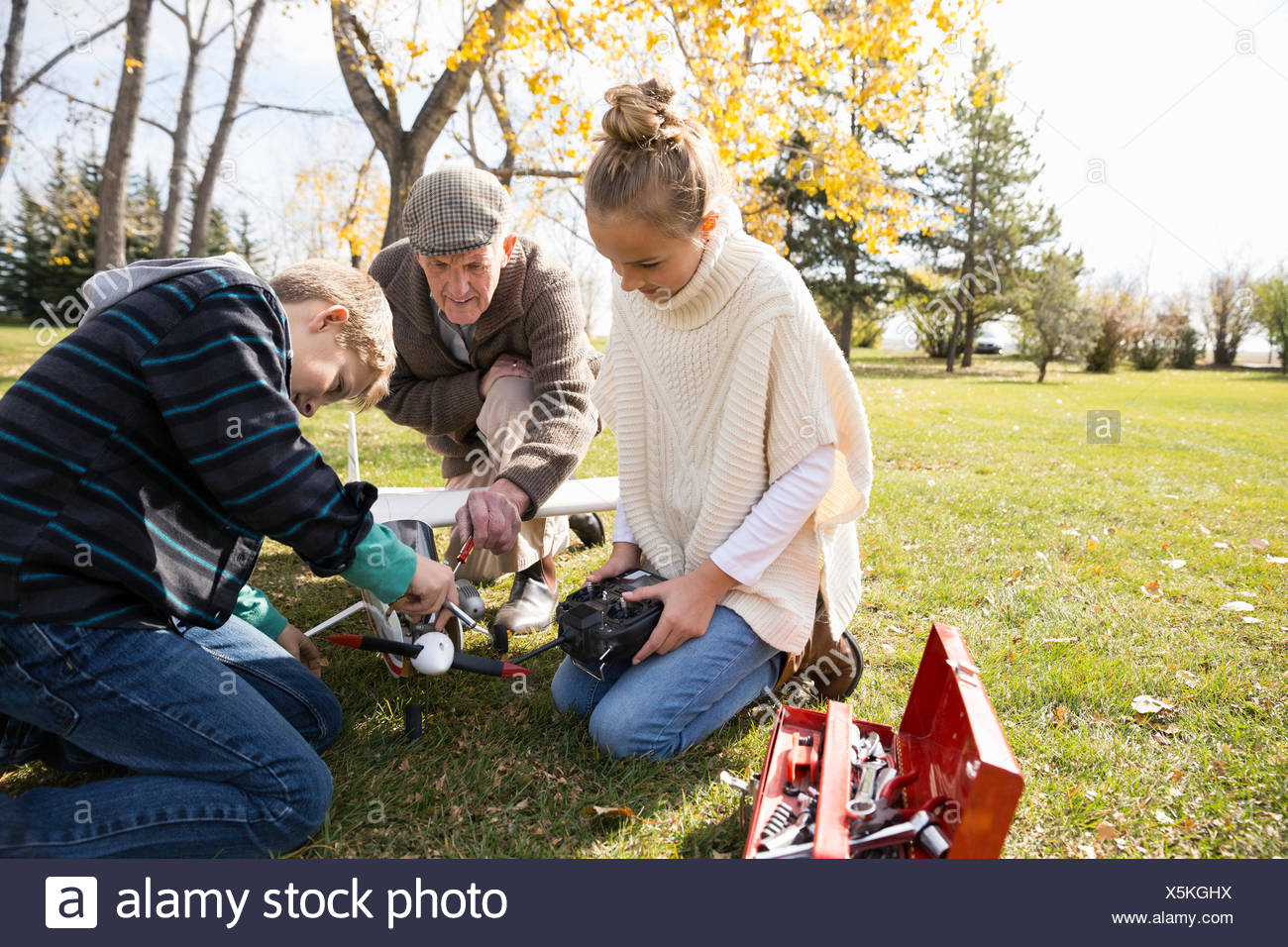 Grandfather and grandchildren fixing model airplane in autumn park - Stock Image
