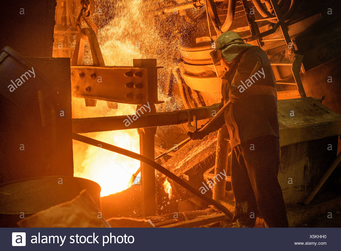 Steel worker looking down at furnace in steel foundry - Stock Image