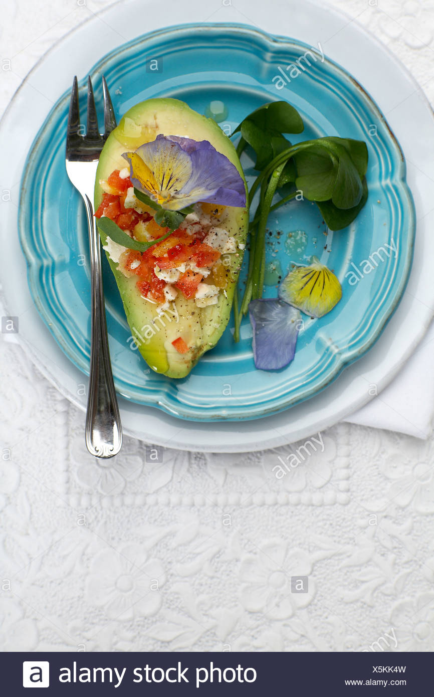 Stuffed avocado with goat's cheese and edible blossoms on plate, elevated view - Stock Image