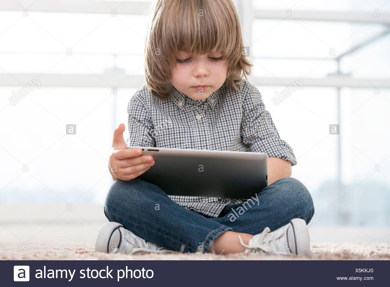 Full length of boy using digital tablet in living room - Stock Image