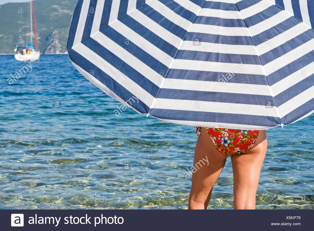 Woman in bikini under striped beach umbrella at ocean - Stock Image