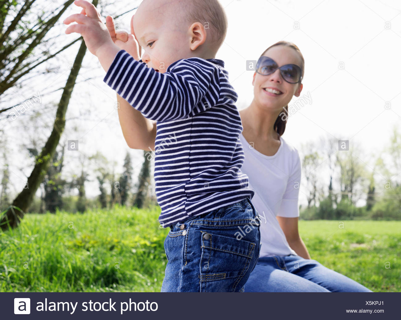 Young mother helping baby son toddle in field - Stock Image