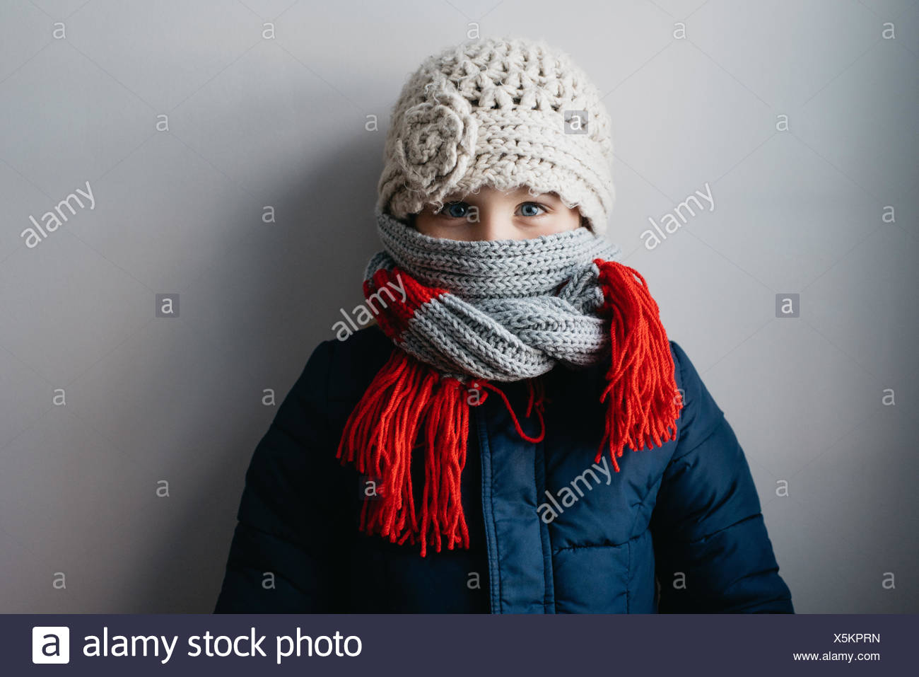 Girl warmly wrapped up in woollen hat and scarf - Stock Image
