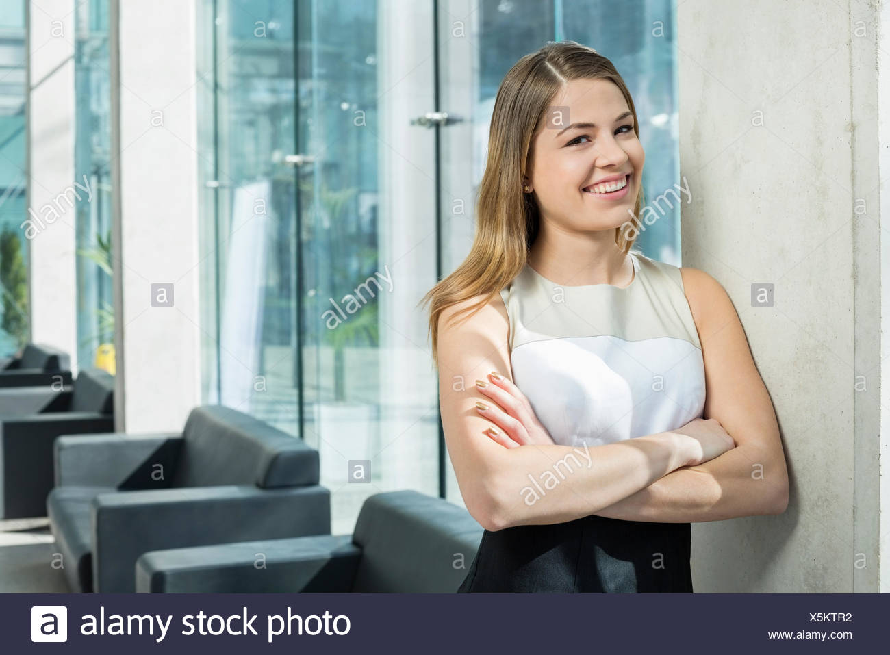 Portrait of happy businesswoman standing arms crossed at office lobby - Stock Image