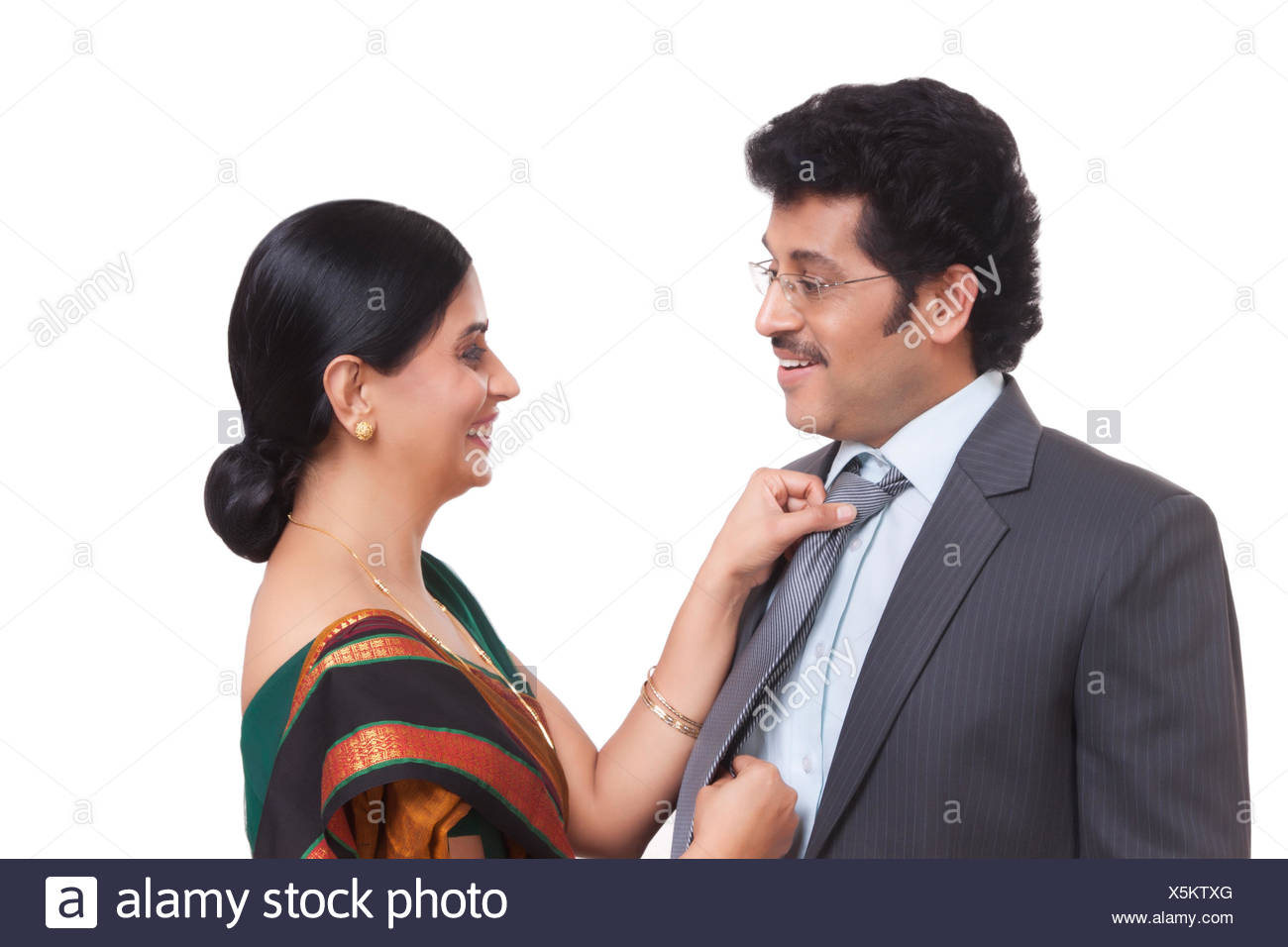 Wife fastening husband's tie - Stock Image