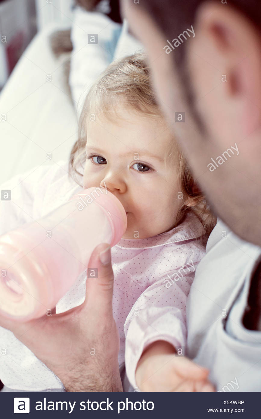 Baby girl drinking from bottle with father's help - Stock Image