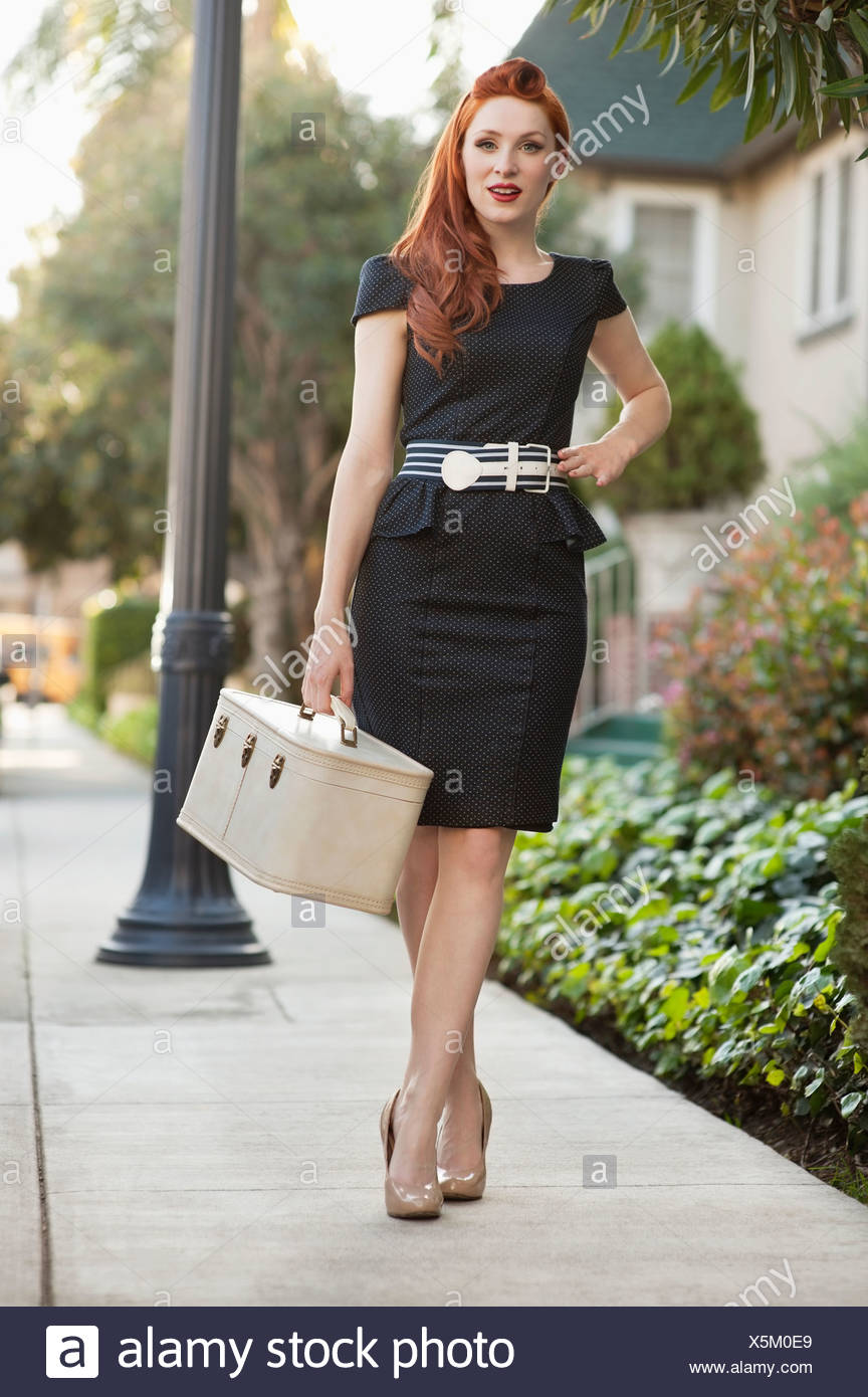 Full length of an elegant woman in a dress walking with a vanity case - Stock Image