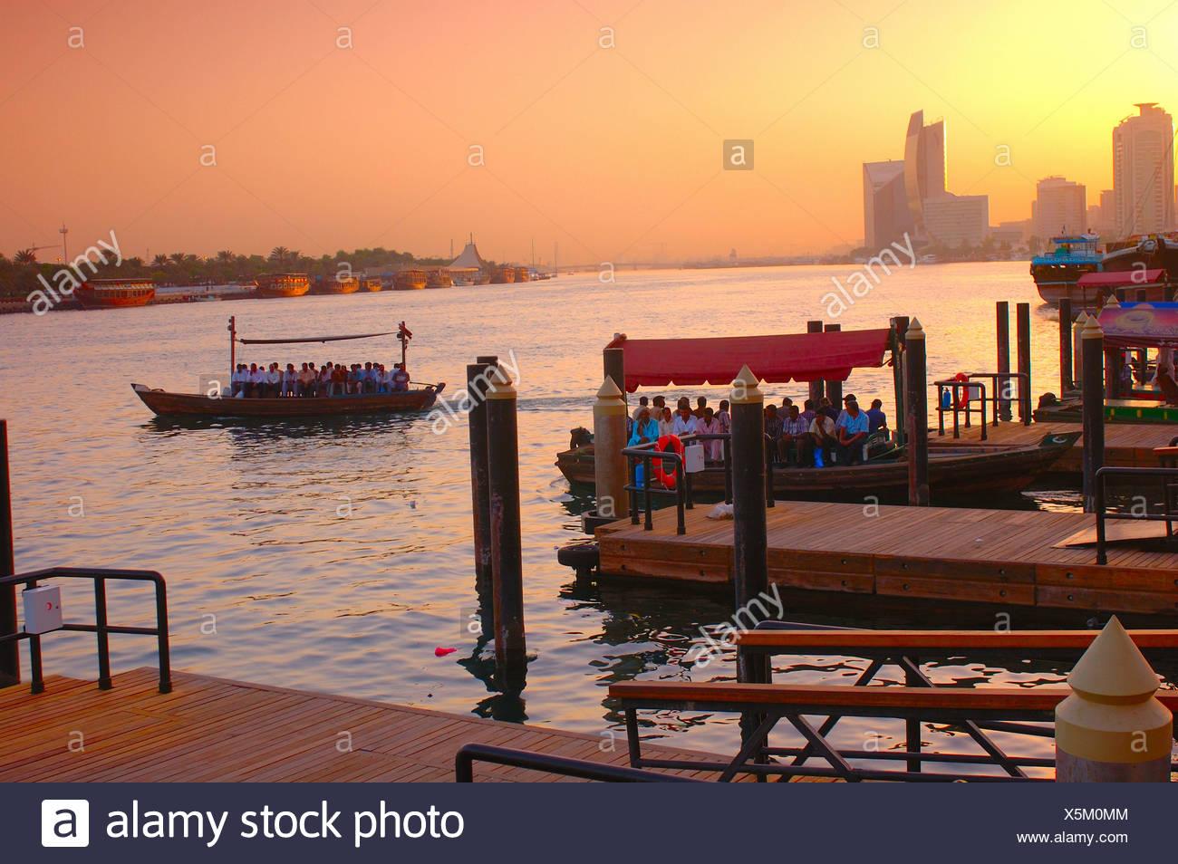 Dubai ferry ferryboat ferries ferryboats people shores coast mood dusk twilight Sabkha Abra station Dubai - Stock Image