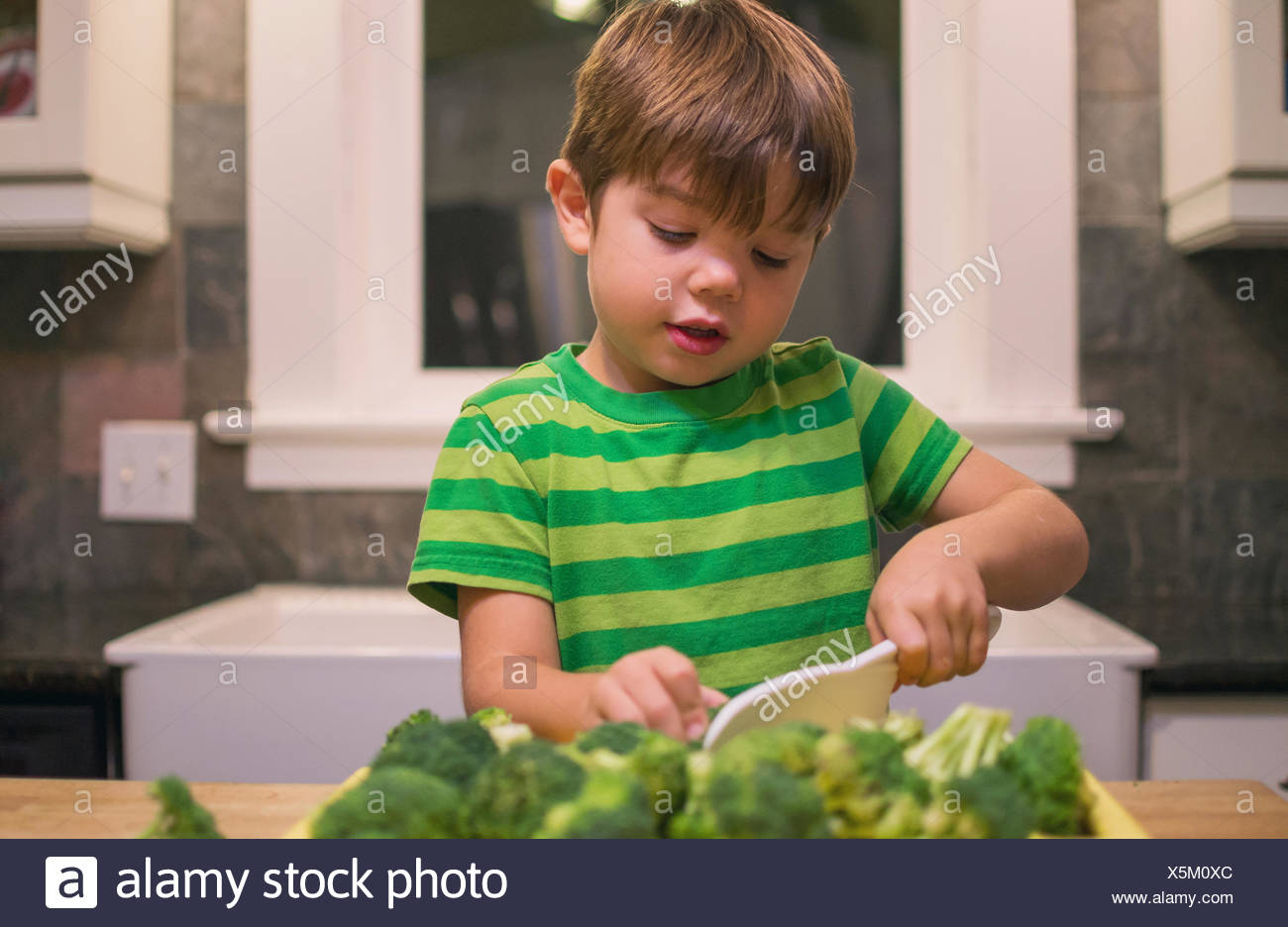 Boy in kitchen chopping broccoli - Stock Image
