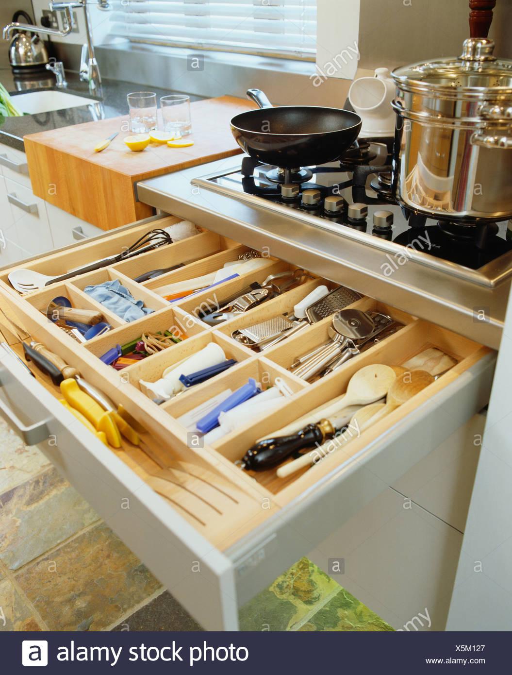 Close Up Of Open Cutlery Storage Drawer Below Pans On Kitchen Hob