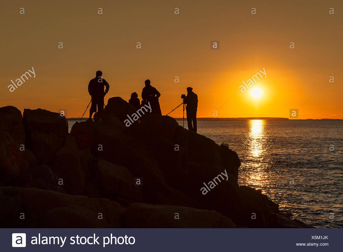 Photographers shooting a coastal sunset, Maine, USA - Stock Image