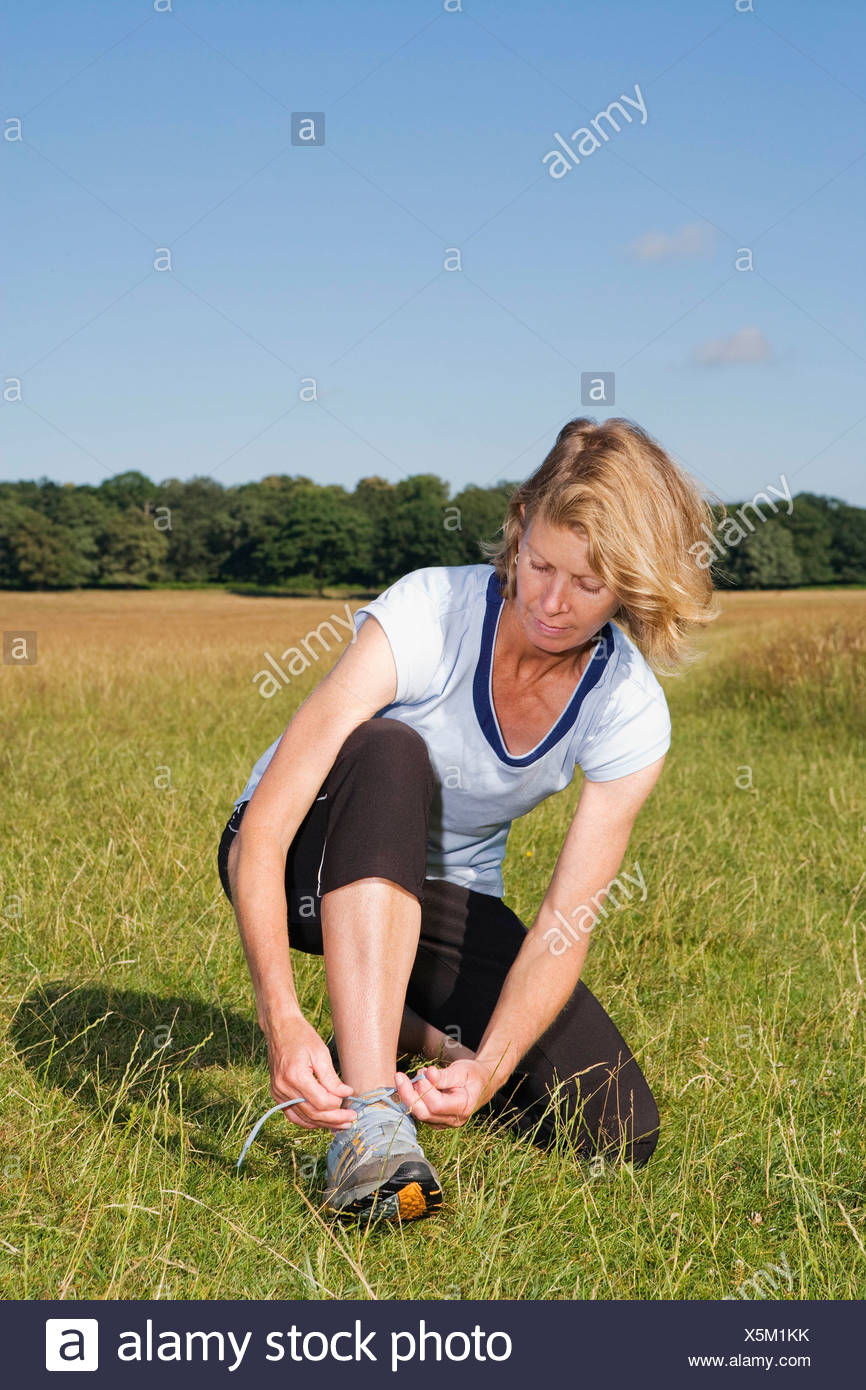Woman runner doing up shoe lace - Stock Image