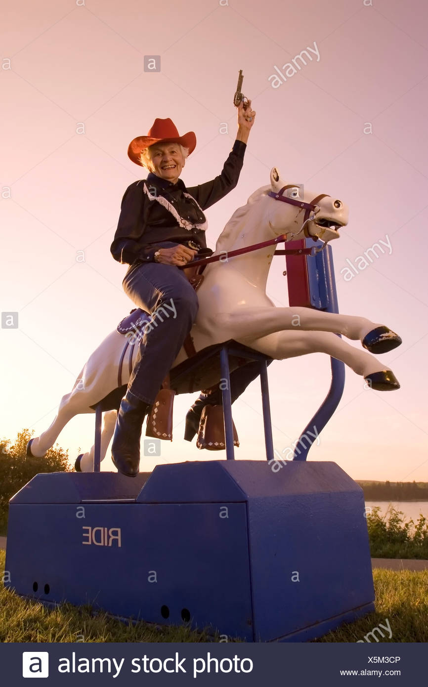 Senior woman riding mechanical horse in cowboy costume, Canada. - Stock Image