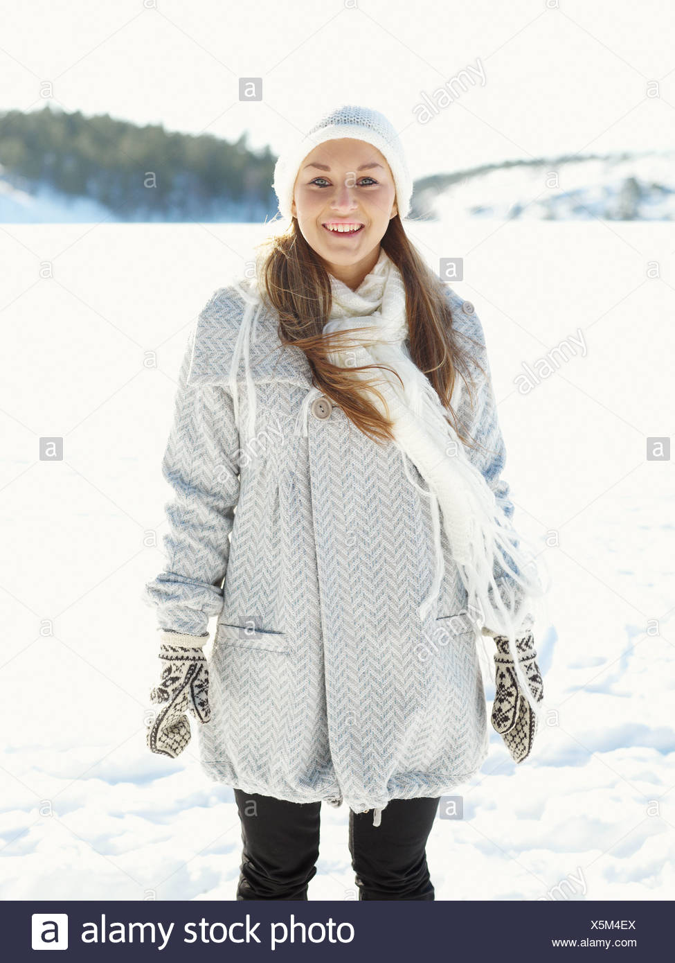 Portrait of young woman wearing white hat and white wooly scarf - Stock Image