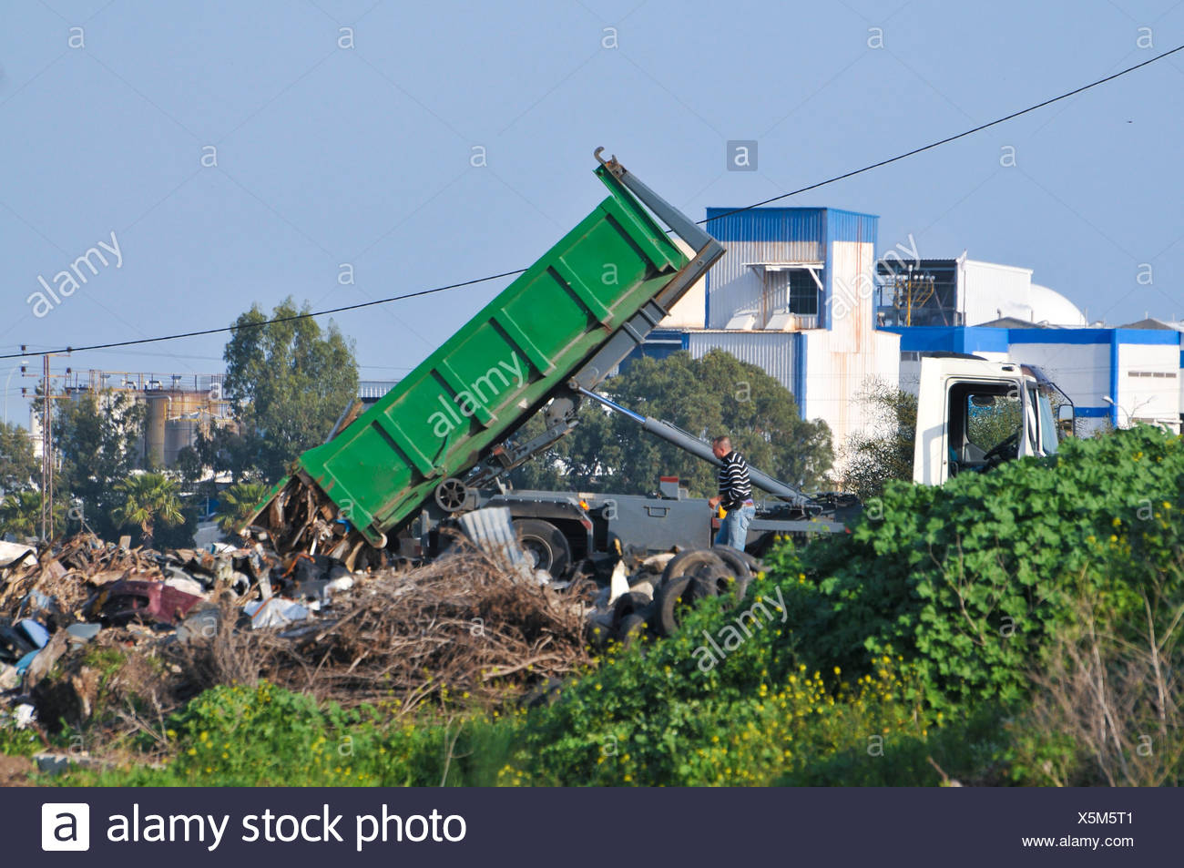Illegal Littering - a truck dumps trash in a vacant field - Stock Image