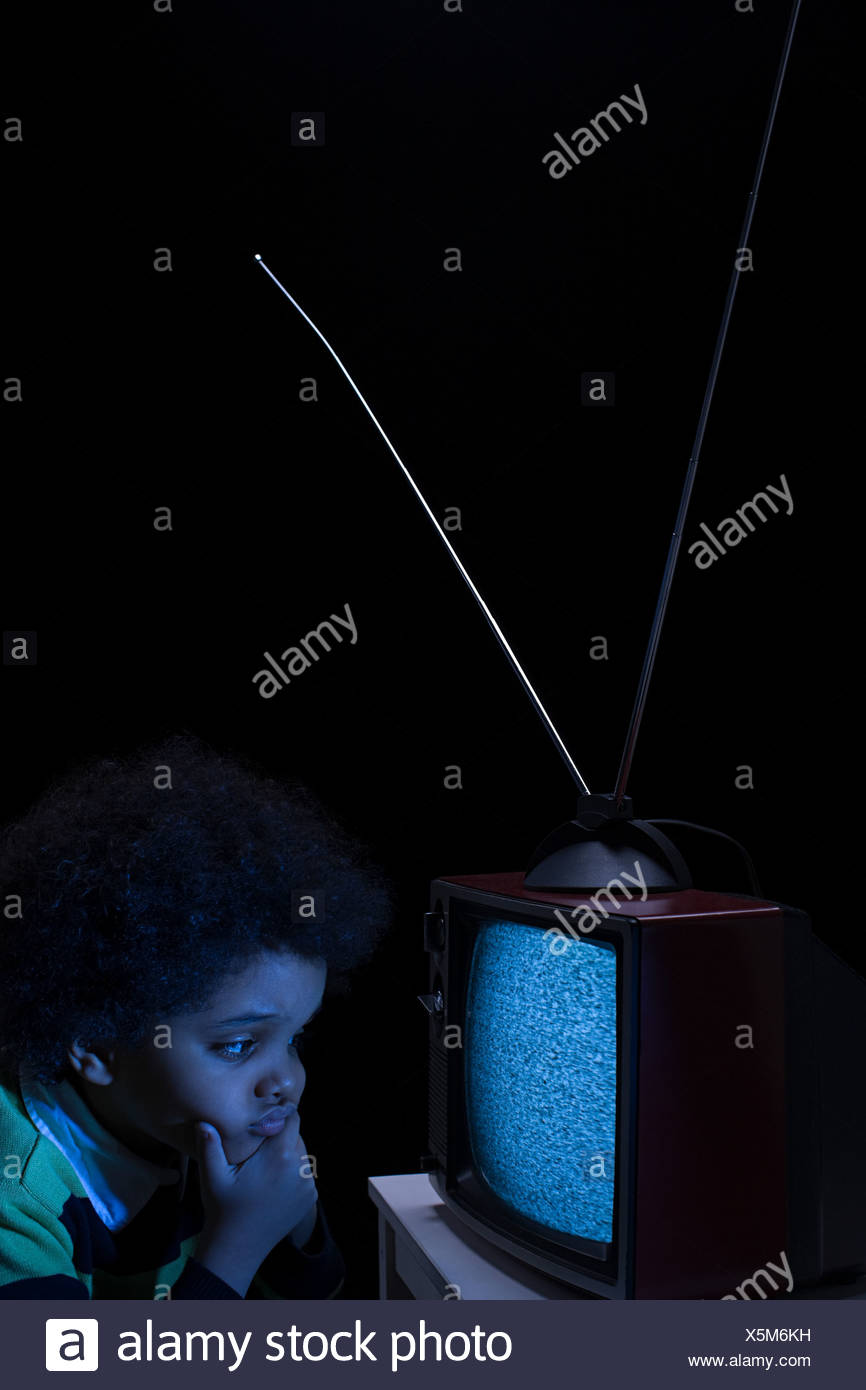 Boy looking at tv screen - Stock Image