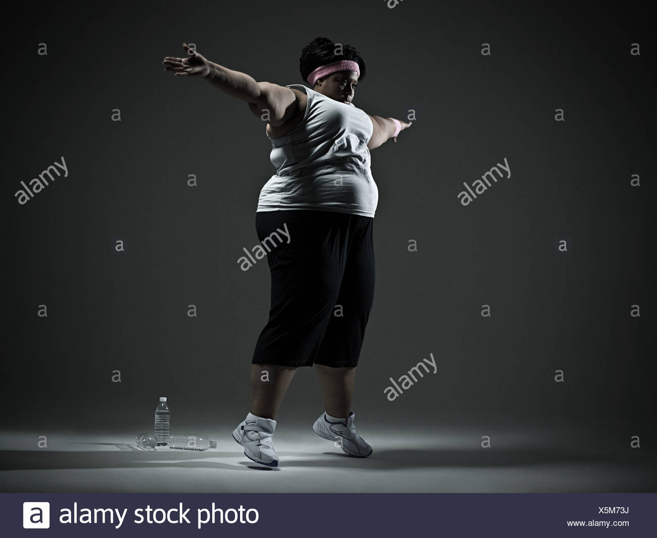 Overweight woman exercising - Stock Image