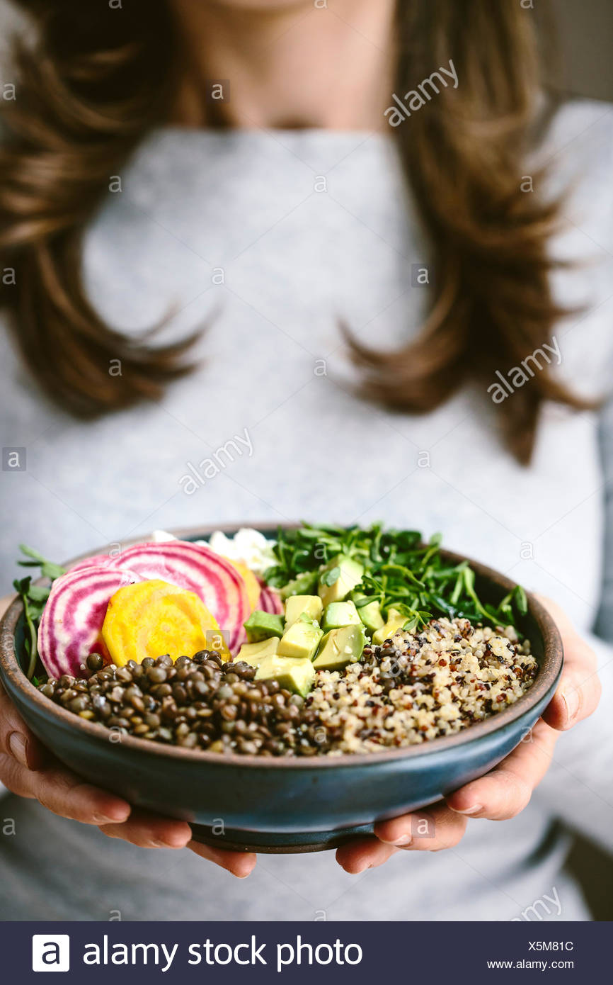 A woman wearing a gray shirt is holding an abundance bowl made up of quinoa, sprouts, lentils, avocados, and chioggia beets. - Stock Image