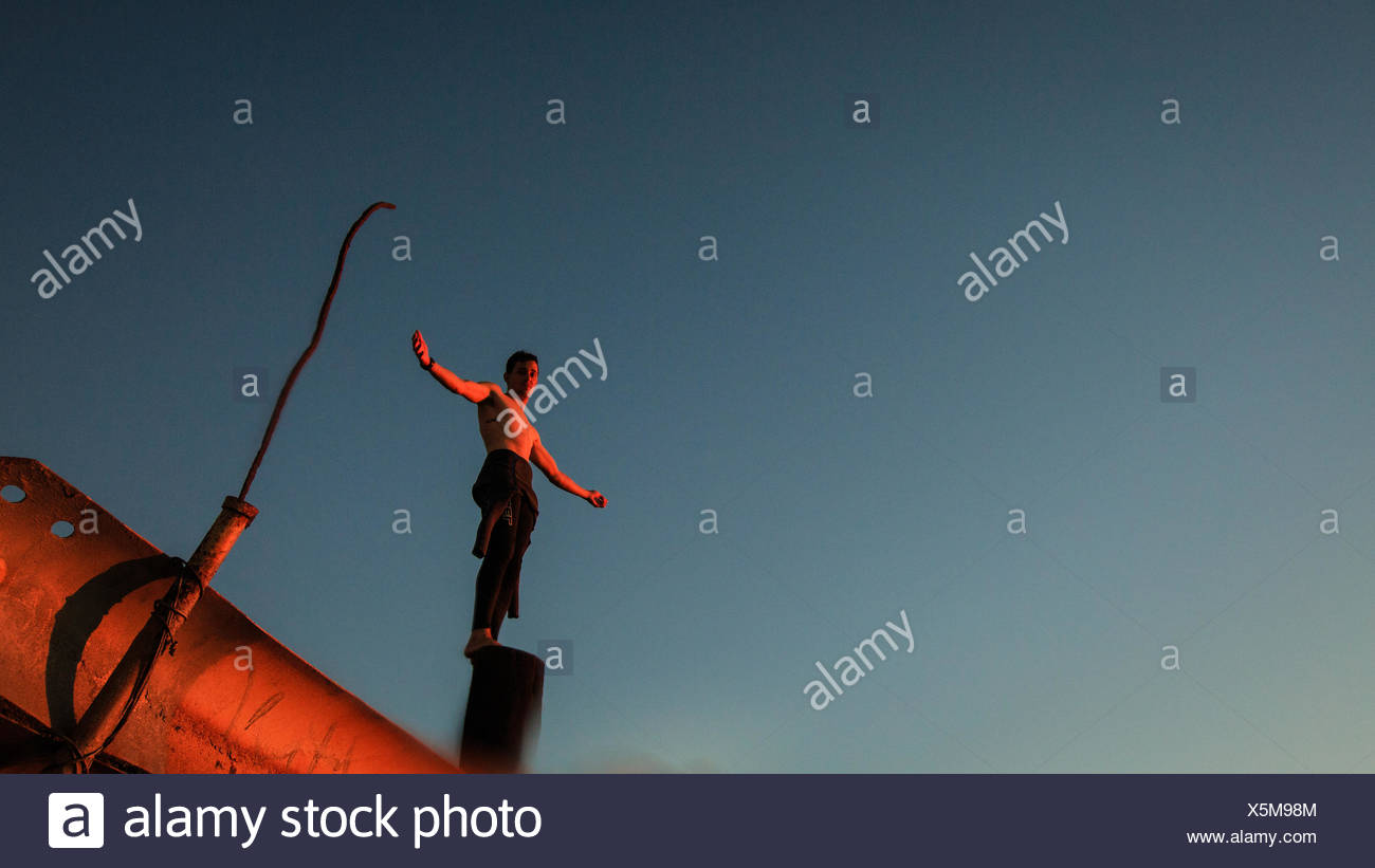 Boy (12-13 years) in wetsuit standing on pole - Stock Image