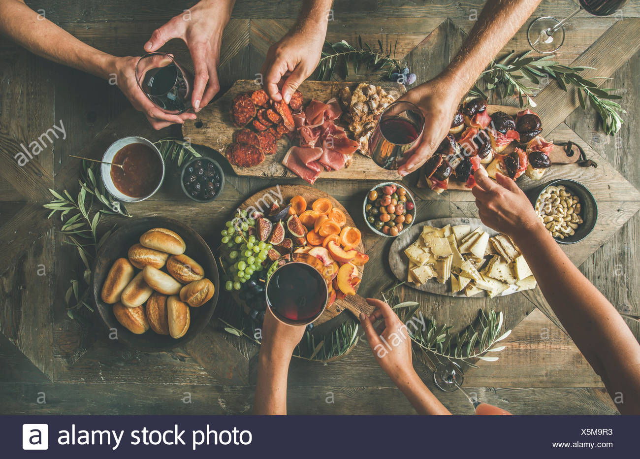 Flat-lay of friends company eating and drinking together. Top view of group of people having party, gathering, celebration or dinner together sitting  Stock Photo