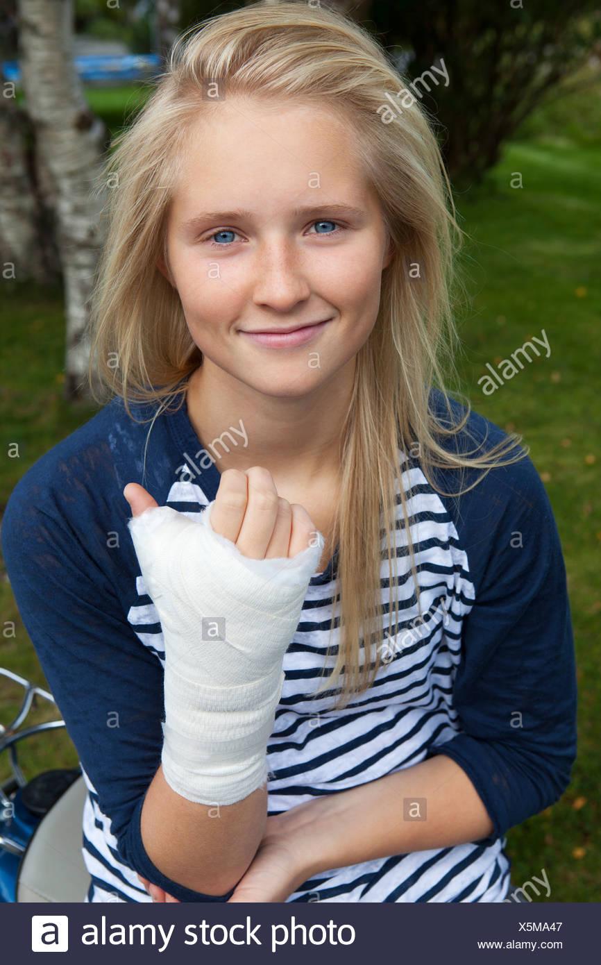 Teenage girl with bandage on hand, smiling, portrait - Stock Image