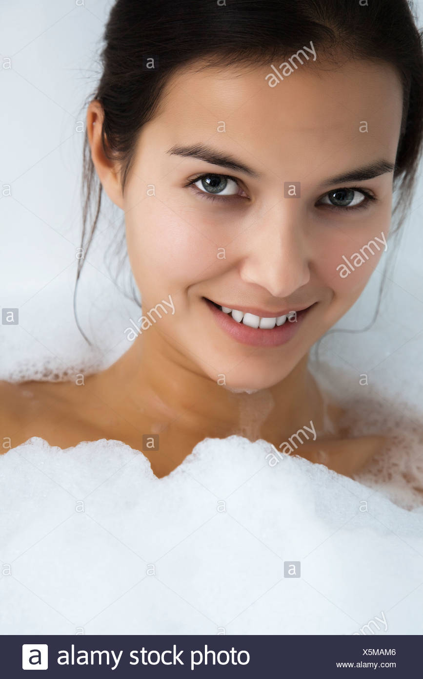 Woman relaxing in bubble bath, portrait - Stock Image