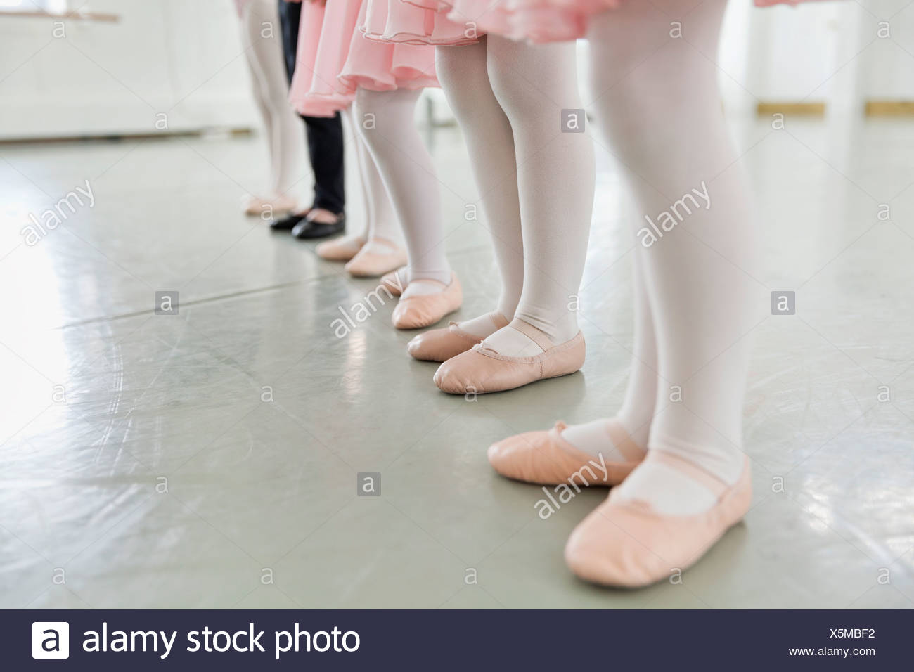 Line of children's feet in ballet slippers in ballet studio Stock Photo