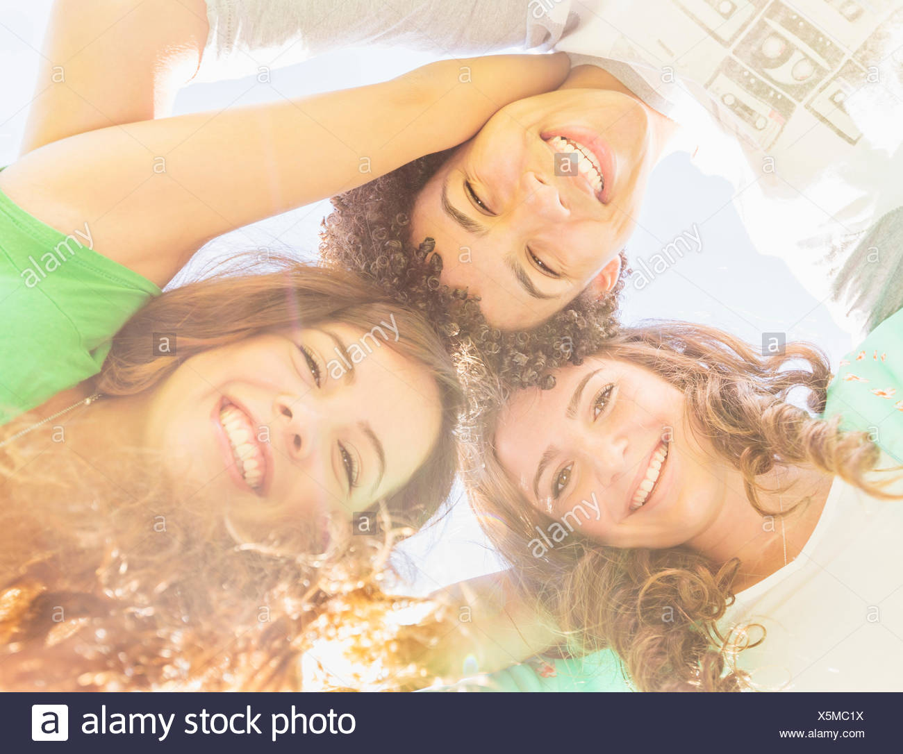 Portrait of friends (14-15) looking down - Stock Image