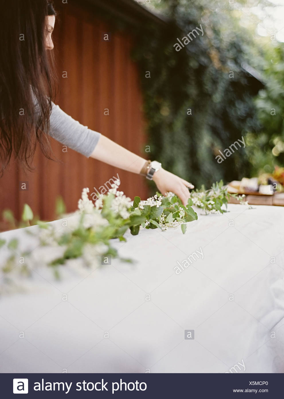 A woman with long hair by table laid outside with a white cloth and central foliage table decoration Place settings - Stock Image