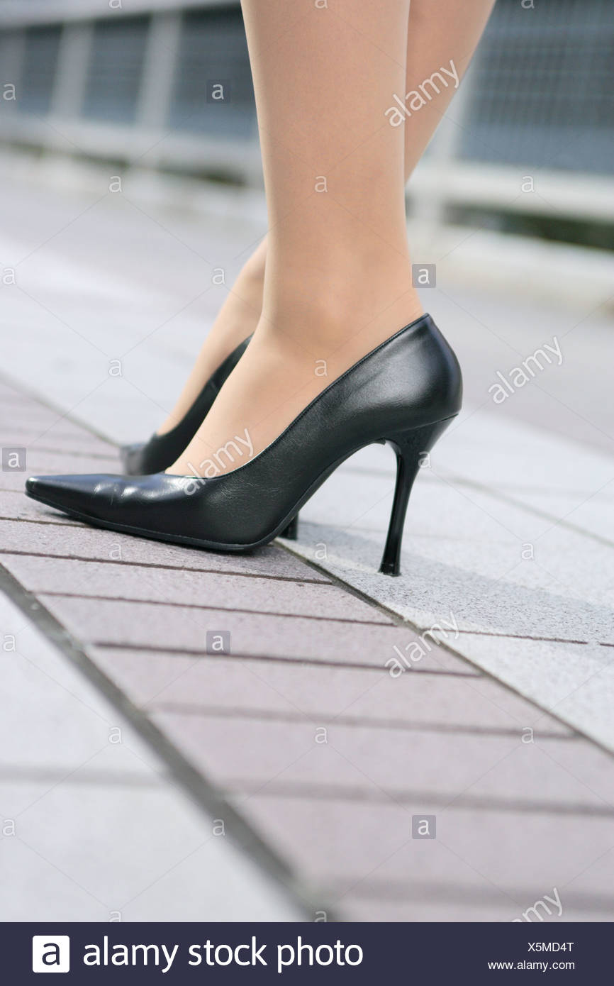 Close-up of a young woman's feet in heels - Stock Image