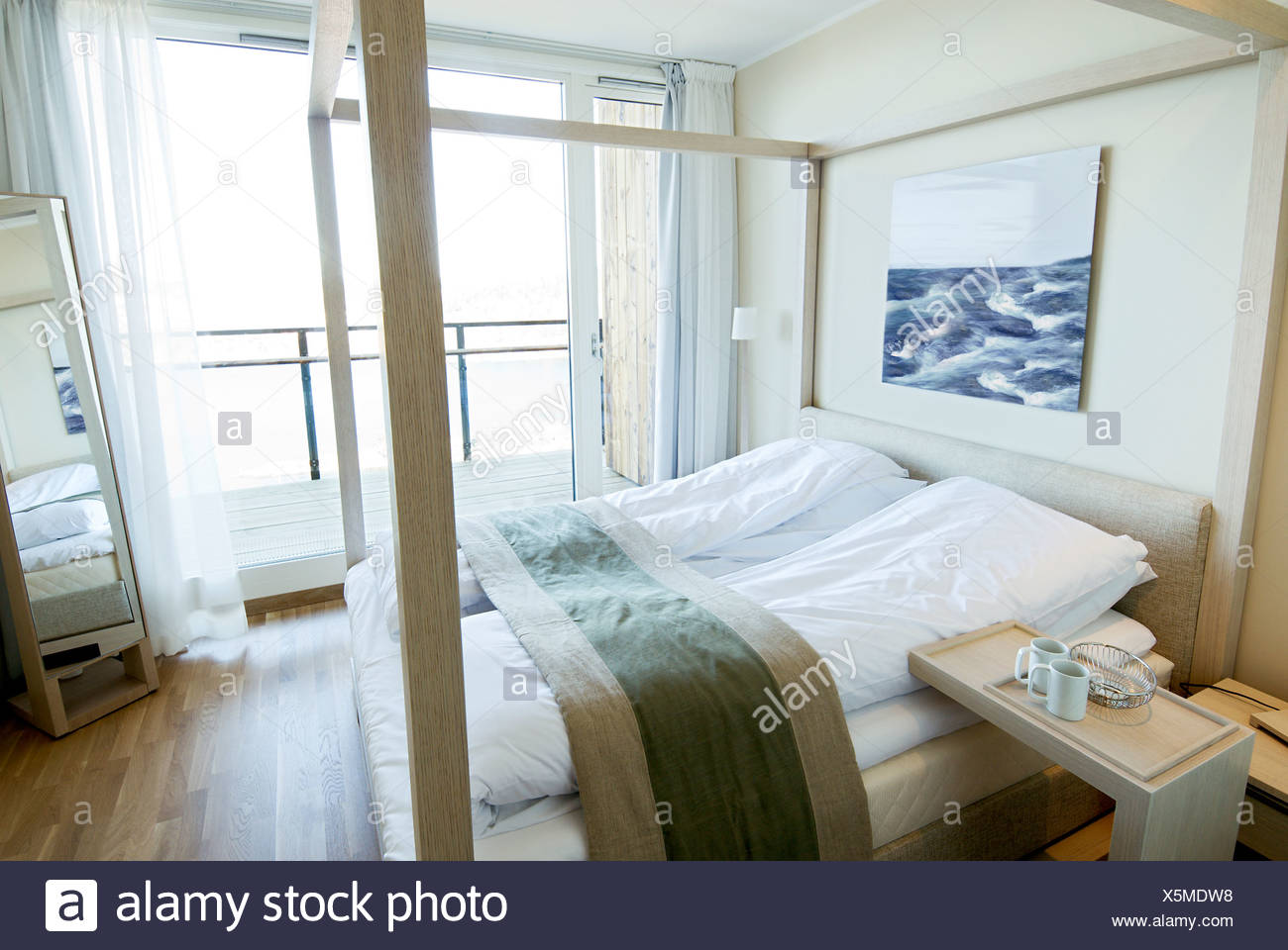 View of a four-post bed on wooden floor by huge window in a bedroom at home - Stock Image