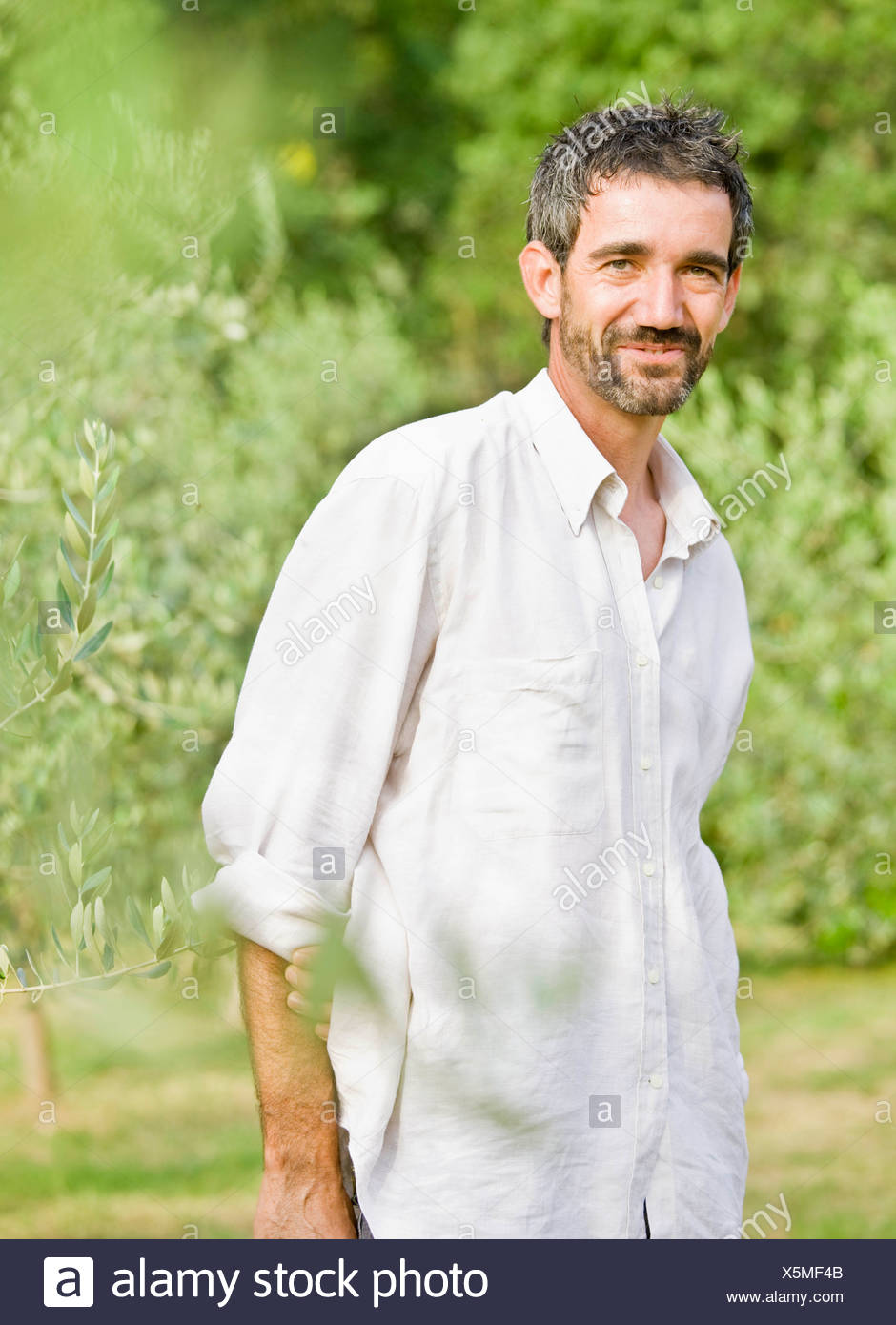 Portrait of man in olive grove - Stock Image