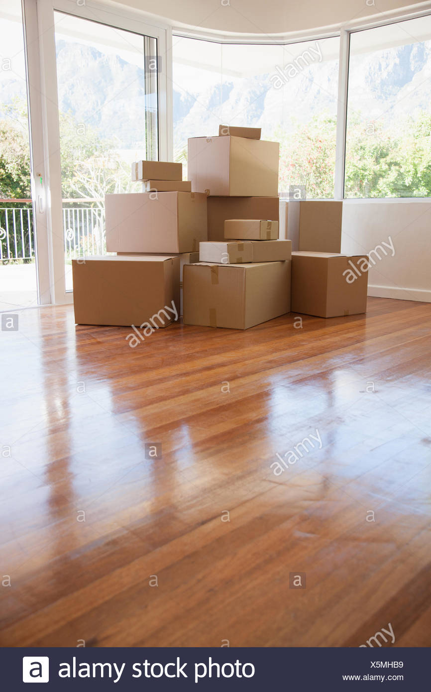 Boxes stacked in living room of new house - Stock Image