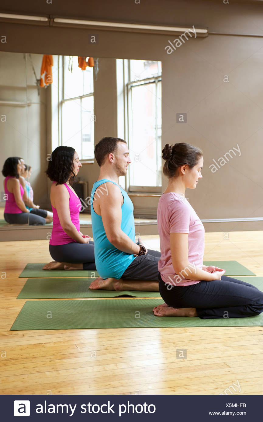 People kneeling in yoga class Stock Photo