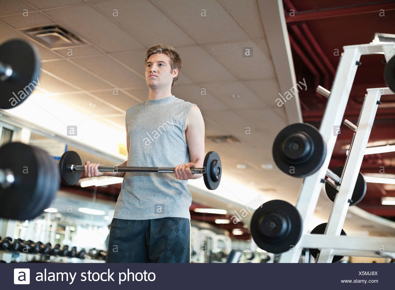 Low angle view of man lifting weights in fitness center - Stock Image